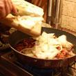 Wrzucanie cebuli na patelnię